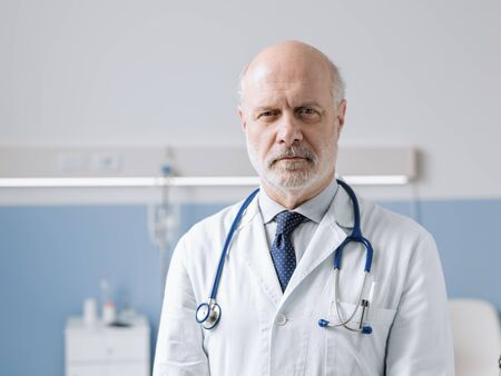 Professional doctor standing next to a hospital bed and looking at camera, healthcare and medicine concept