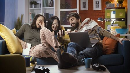 Friends sitting on the sofa at home and social networking with a smartphone, they are laughing and watching videos together