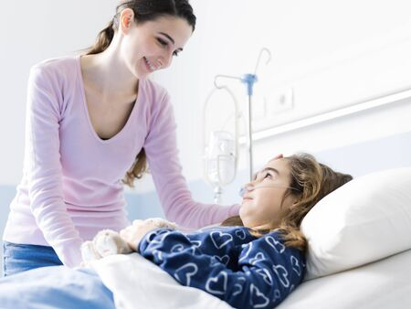 Young woman assisting her sick child lying in bed at the hospital, pediatrics and healthcare concept