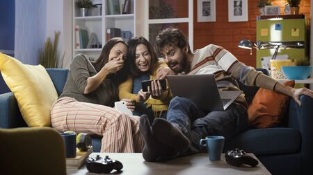 Friends sitting on the sofa at home and social networking with a smartphone, they are laughing and watching videos together Stockfoto - 147427270