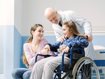 Professional doctor assisting a patient on wheelchair and her mother at the hospital Stockfoto - 147427271