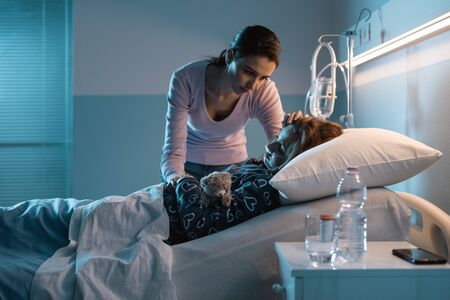 Young mother assisting her young child lying in a hospital bed at night, she is worried and caressing her head Stockfoto - 147427272