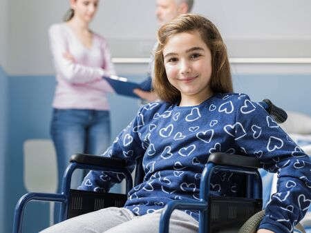 Smiling girl in wheelchair at the hospital, her mother and the doctor are talking in the background Stockfoto - 147427273