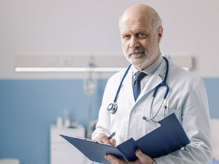 Professional doctor working at the hospital, he is writing medical records on a clipboard Stockfoto - 147306611