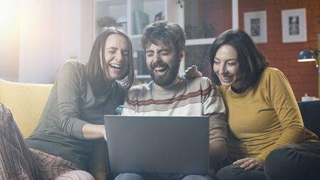 Cheerful friends sitting on the sofa at home and connecting online with their laptop, they are social networking and having fun Stockfoto - 147427276