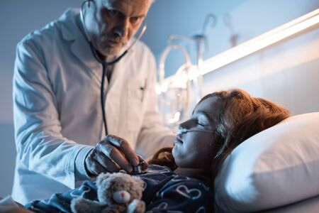 Professional doctor examining a child lying in a hospital bed at night, he is using the stethoscope and checking her breath 版權商用圖片