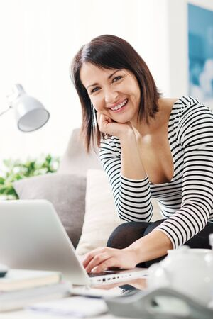 Woman relaxing at home, she is sitting on the couch, using a laptop and connecting to the internet 版權商用圖片