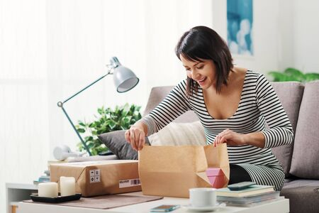 Happy excited woman at home, she has received a postal parcel and she is unboxing her gift, delivery and online shopping concept Stockfoto - 147427277