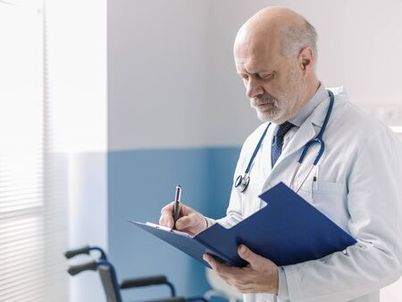 Professional doctor working at the hospital, he is writing medical records on a clipboard 版權商用圖片
