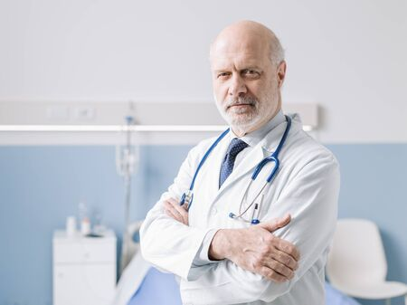 Professional doctor standing next to a hospital bed and posing with folded arms, healthcare professionals and medicine concept