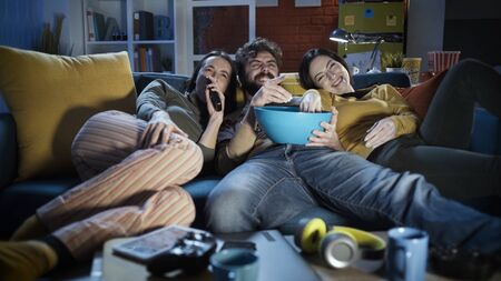Friends sitting on the sofa at home, they are watching movies and eating popcorn together Stockfoto