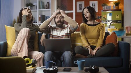 Friends sitting on the sofa at home and watching sports online, they are disappointed and frustrated