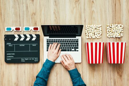 Man watching a film streaming online with popcorn, 3D glasses and clapboard on wooden table Stockfoto