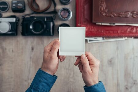 Photographic equipment, cameras and photo albums on a vintage desktop, a photographer is holding a blank instant photo Stockfoto - 147805799