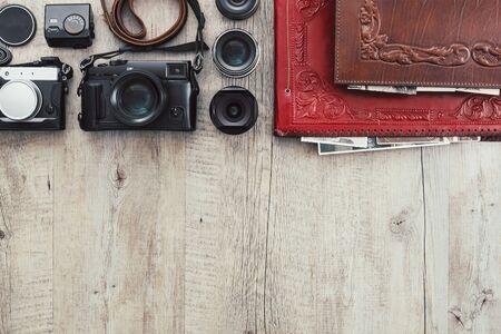 Photographic equipment, cameras, photo album and digital tablet on a vintage desktop