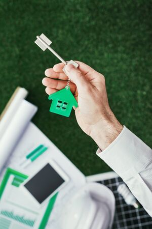 Real estate agent holding your new house keys, solar panel and drafts on the background, housing and green building concept Stockfoto - 147806238