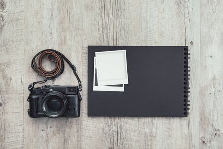 Professional digital camera, instant pictures and photo album on a wooden desktop, art and photography concept Stockfoto - 147806160