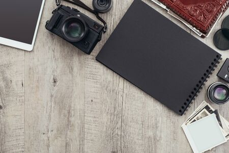 Photography equipment and camera on a desktop, a photographer is holding a picture and creating a photo album Stockfoto - 147810527