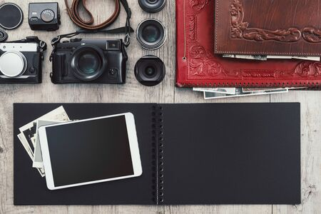 Photographic equipment, cameras, photo album and digital tablet on a vintage desktop Stockfoto - 148582541