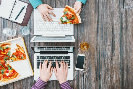 Business people working at office desk and having a lunch break with a tasty pizza