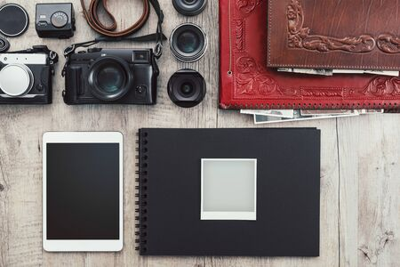 Photographic equipment, cameras, photo album and digital tablet on a vintage desktop Stockfoto - 148582545