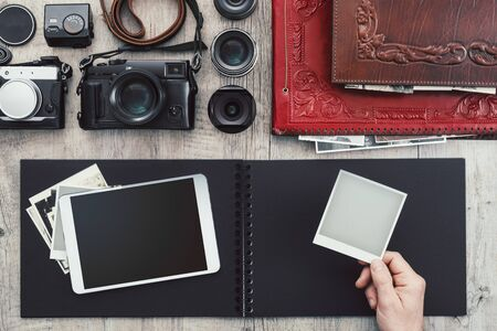 Photographic equipment, cameras, photo album and digital tablet on a vintage desktop Stockfoto - 148582546