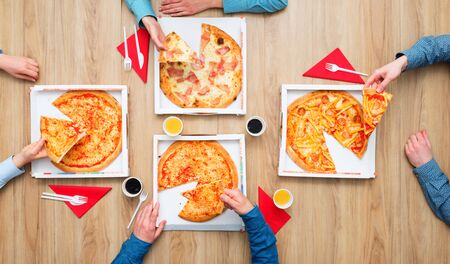Group of friends having a pizza party at home and enjoying together, they are holding pizza slices, flat lay Stockfoto - 147806266