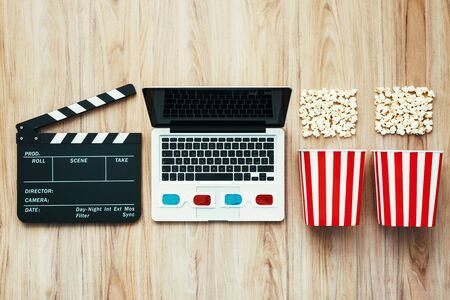 Laptop, clapper board, popcorn and 3D glasses: cinema streaming and movie series online concept Stockfoto - 147807250