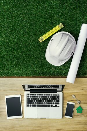 Energy efficient house design and construction, desktop with house project, folding meter, laptop and safety helmet Stockfoto - 147807578
