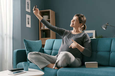 Happy pregnant woman sitting on the sofa at home and taking selfies with her smartphone Stockfoto