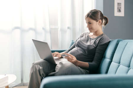 Pregnant woman sitting on the sofa and doing online shopping at home, she is connecting with her laptop and using a credit card