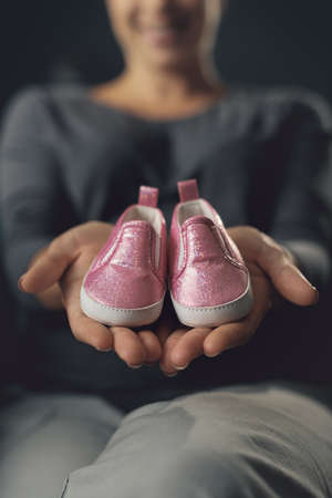 Pregnant woman showing cute baby shoes, pregnancy and motherhood concept