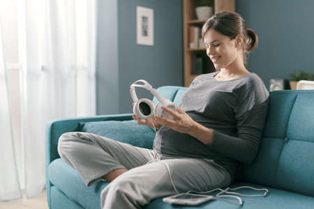 Happy pregnant woman holding headphones close to her belly and playing music for her baby, pregnancy and lifestyle concept 版權商用圖片 - 158770436