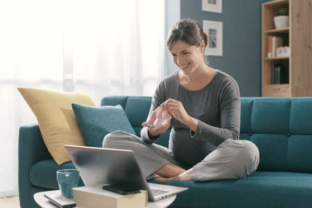 Cheerful pregnant woman sitting on the sofa at home and video calling online, she is showing cute baby shoes, pregnancy and lifestyle concept
