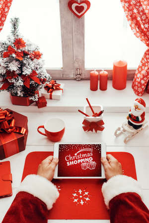 Santa Claus waiting for Christmas and connecting with a digital touch screen tablet in front of a window, point of view shot Stockfoto