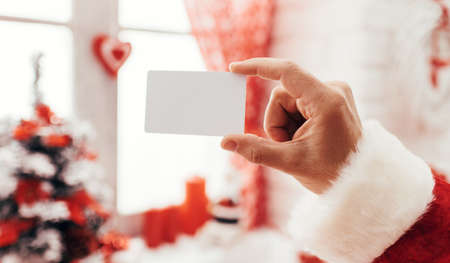 Santa Claus holding a blank business card, window and Christmas decorations on the background