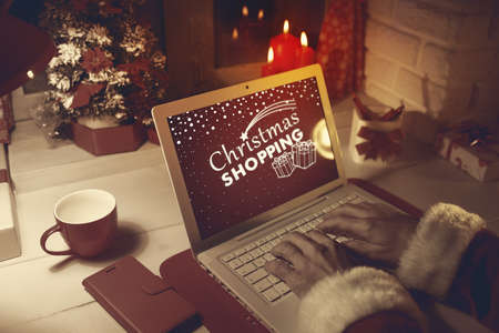 Santa Claus at home, he is connecting late at night with his laptop, Christmas and celebrations concept