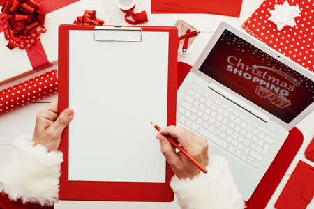 Santa Claus planning for Christmas, he is writing on a clipboard, using a laptop, and wrapping gifts, blank copy space, top view