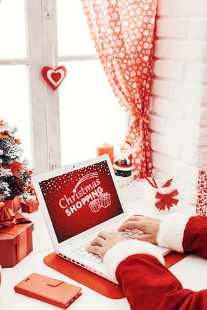 Santa working at desk and networking with a laptop, he is connecting to the internet and preparing for Christmas, holidays and technology concept