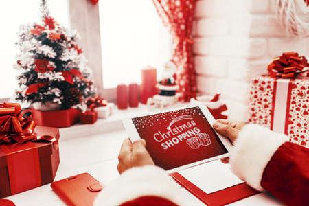 Santa Claus working at desk and using apps on a touch screen tablet, Christmas and technology concept