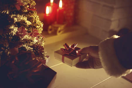 Santa Claus bringing a beautiful gift during Christmas eve's night, hand close up, lit candles on the background