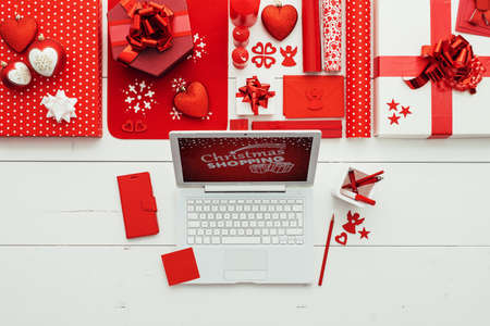 Preparing for Christmas: laptop, gifts, decorations and wrapping paper rolls on a white wooden table, flat lay 版權商用圖片 - 160530440