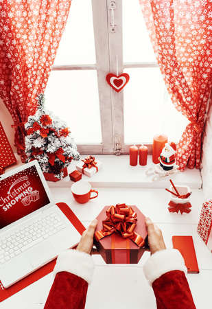 Santa Claus sitting at his desk and holding a beautiful gift box with a ribbon, Christmas and holidays concept, point of view shot Stockfoto