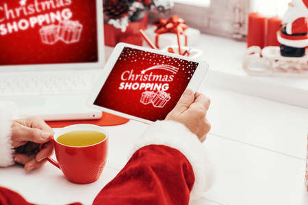 Santa Claus waiting for Christmas and connecting with a digital touch screen tablet, he is drinking a cup of coffee