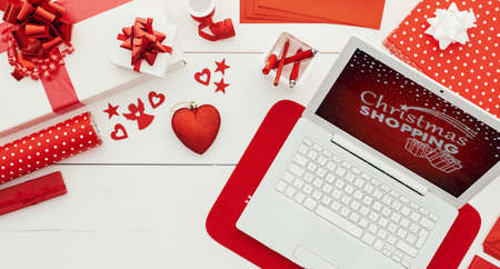 Preparing for Christmas: laptop, gifts, decorations and wrapping paper rolls on a white wooden table, flat lay Stockfoto