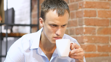 young attractive man drinking a coffee  in creative work space Stock Photo