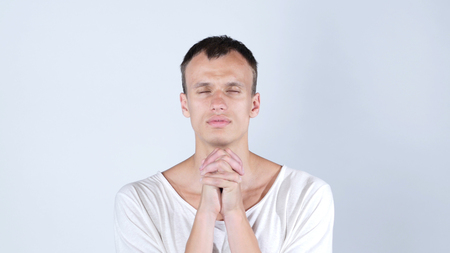 Closeup portrait of young man, praying looking up hoping for best , forgiveness Stock Photo