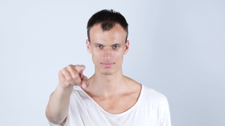 to prefer: Portrait of a young man pointing his finger at you