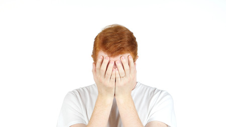 Depressed Man with Problems holding hand over his Face
