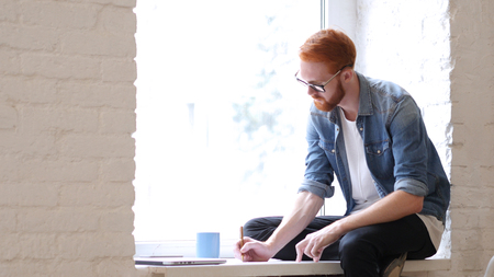 Designer Writing and Working on New Design, Sitting in Window, Red Hairs and Beard